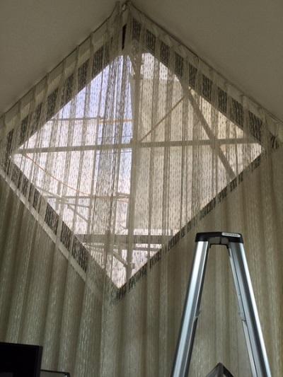 窓の傾斜に沿わせたレールにレースのカーテン
